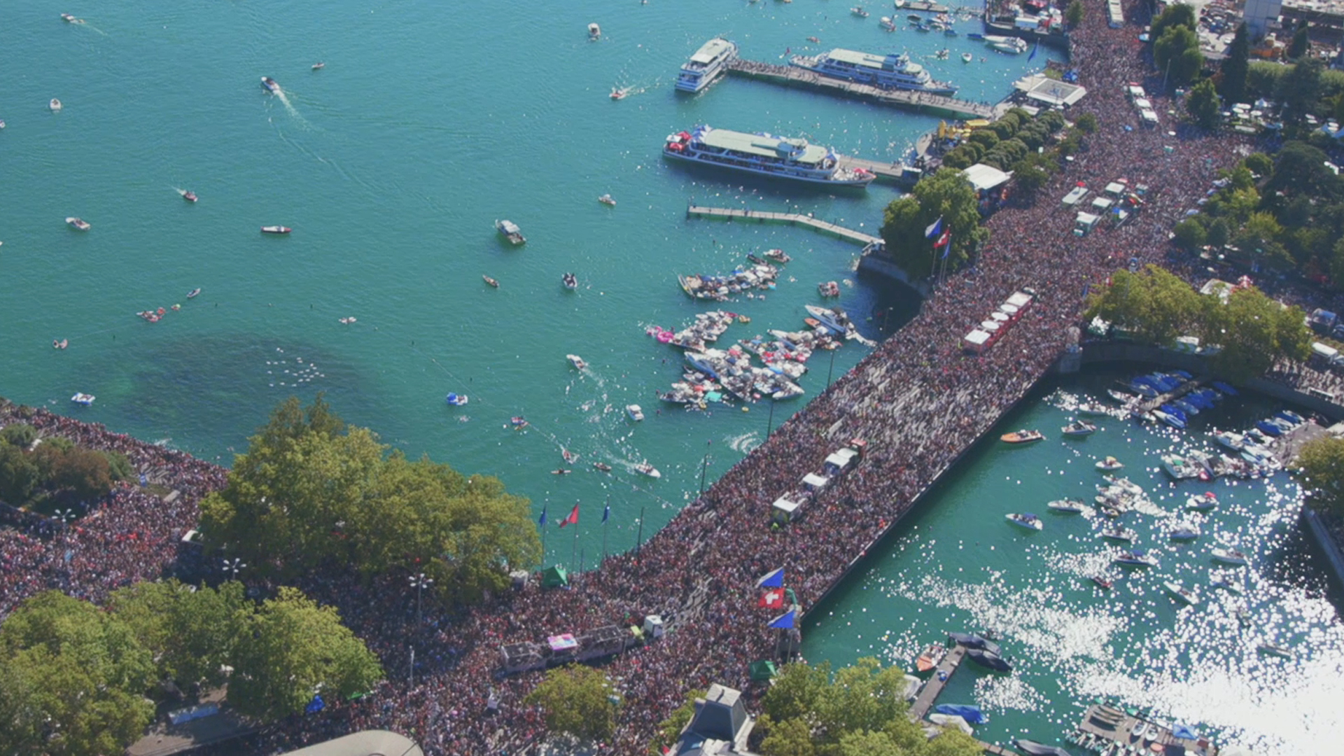 Streetparade seen from a Helicopter above the bridge crossing the river, thousands of people on the bridge