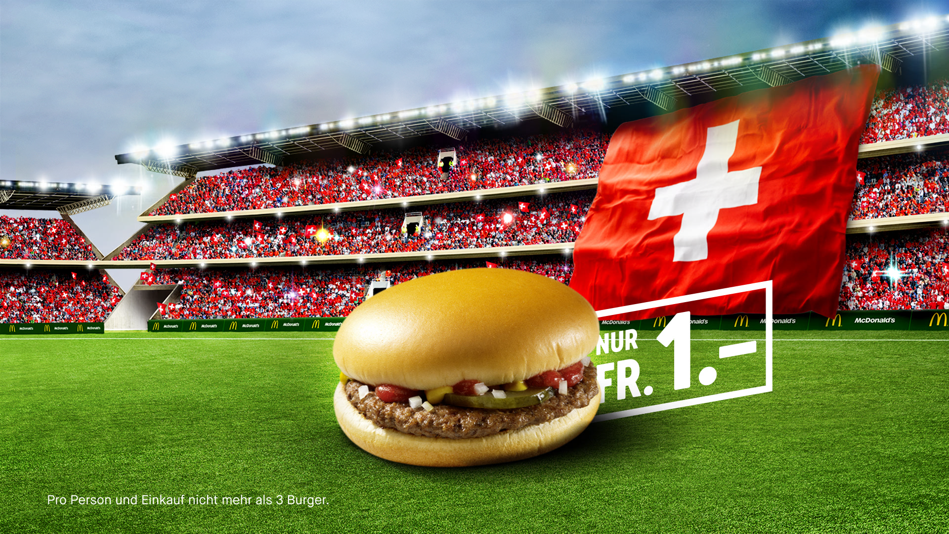 A McDonald's Hamburger in a Soccer stadium with the Swiss flag in the background