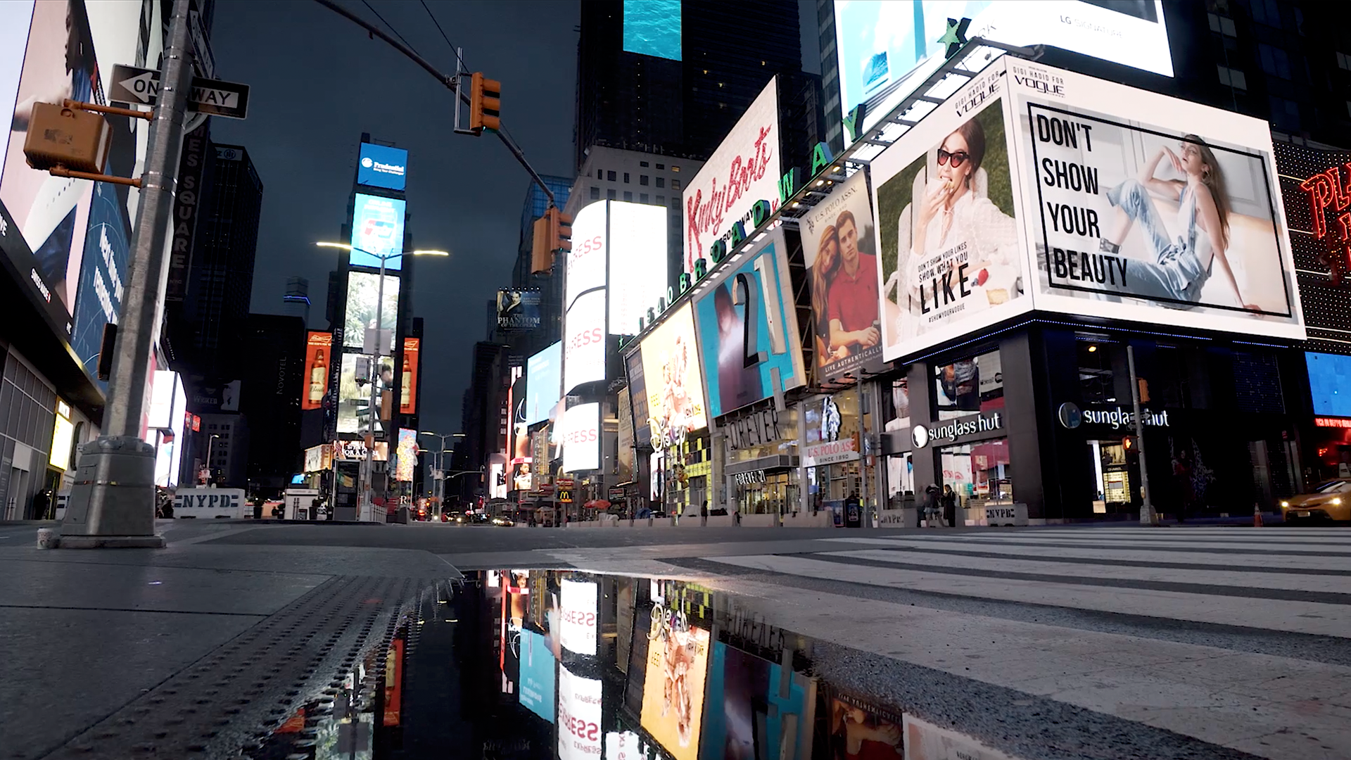 New York City Street view with illuminated Ad displays in the background, reflecting in a small water pond on the street