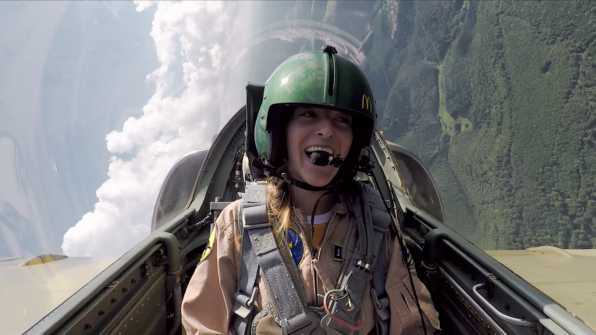 Am excited girl sitting inside a fighter jet, flying a curve above trees