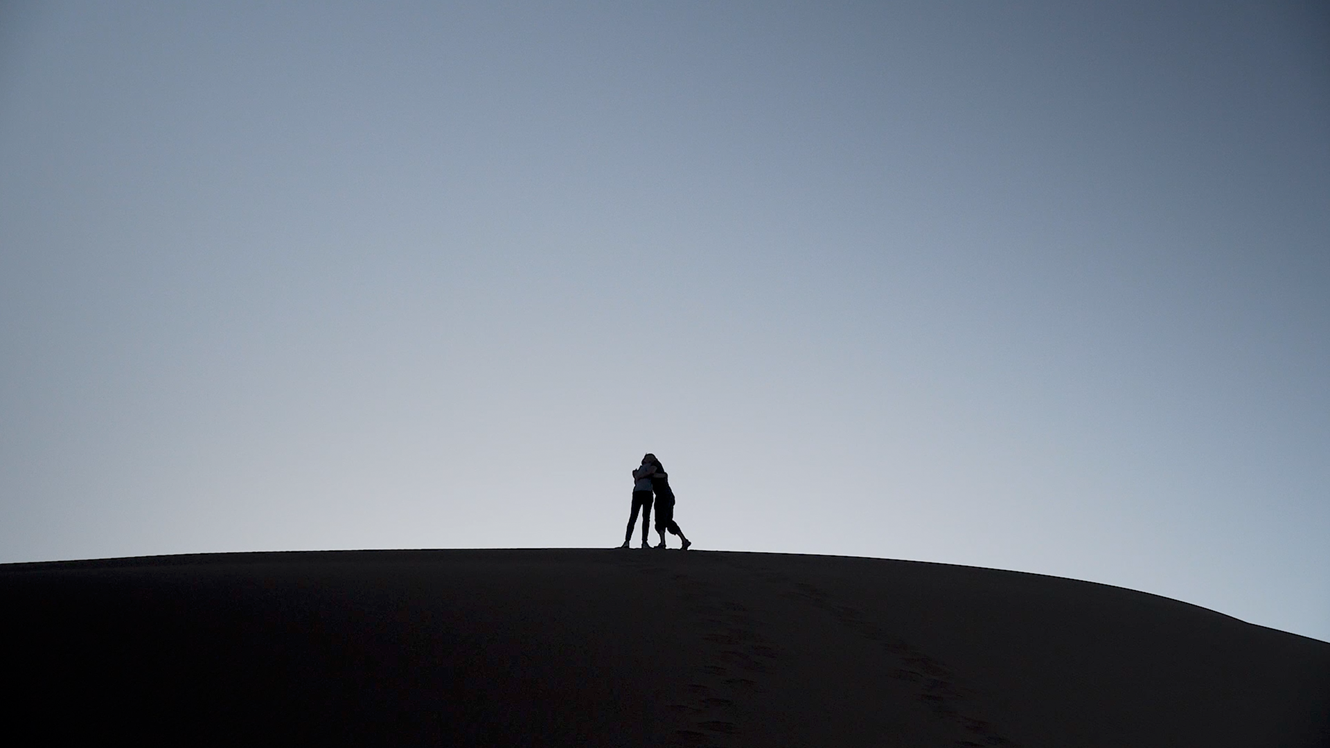 2 people seen as a silhouette standing on a dune in the moroccan dessert in the evening