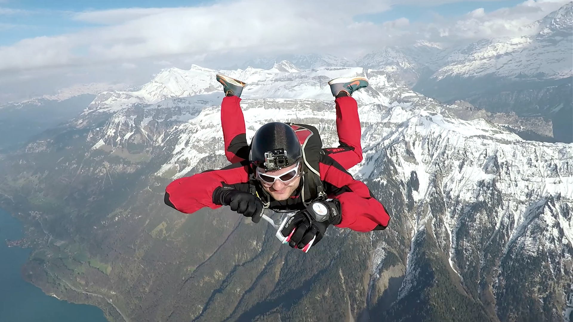 Front view of a skydiver on 3000 feet, eating a McFlurry with snow covered mountains and a lake in the background