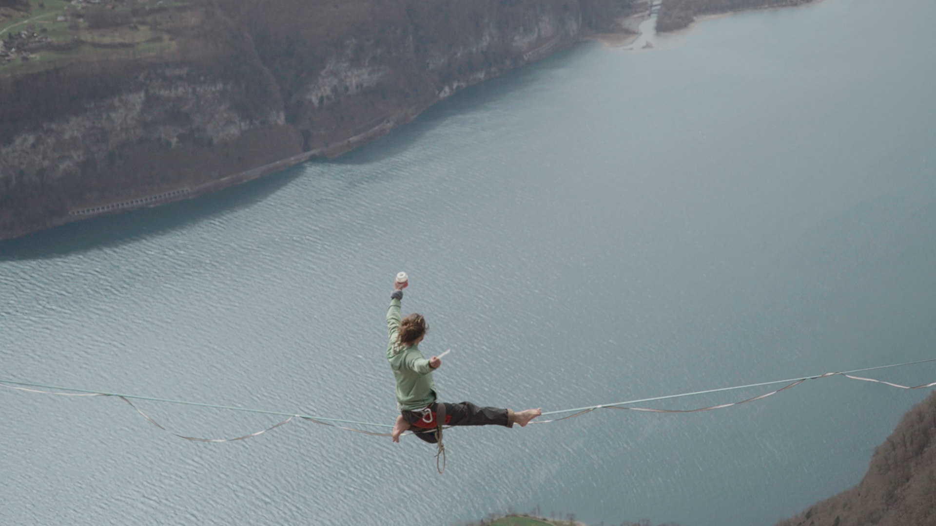 A Slackliner on a rope, holding a McFlurry with a lake 1000 feet beneath him