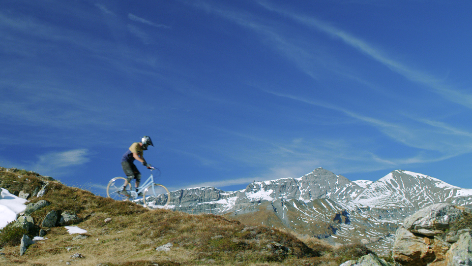 Man riding a city bike down a mountain