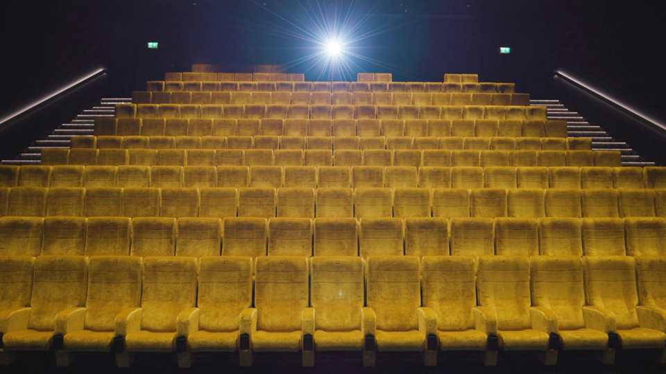 Empty Cinema dimly lit with yellow seats